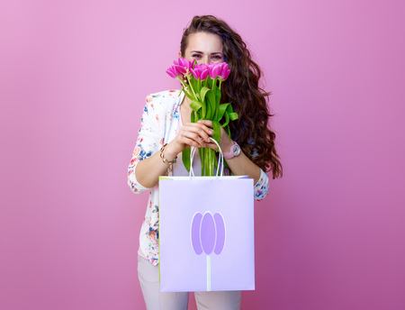 Pink Mood. young woman with long wavy brunette hair isolated on pink with shopping bag hiding behind a bouquet of tulips