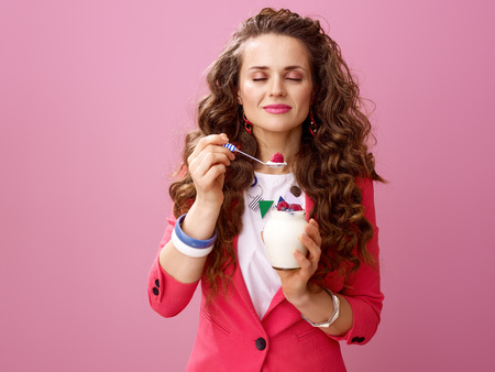 Pink Mood. relaxed stylish woman with long wavy brunette hair isolated on pink background enjoying farm organic yogurt Фото со стока