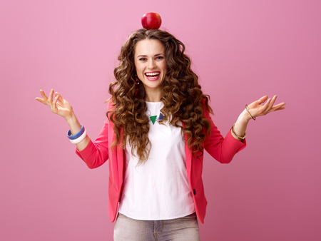 Pink Mood. smiling stylish woman with long wavy brunette hair on pink background with an apple on head
