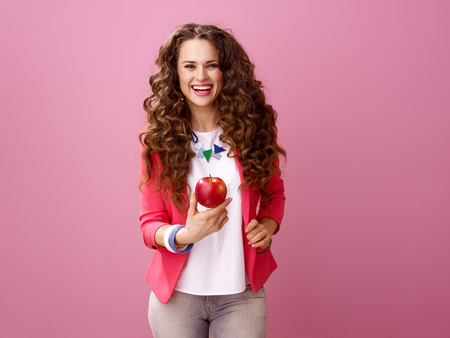 Pink Mood. happy modern woman with long wavy brunette hair on pink background showing an apple