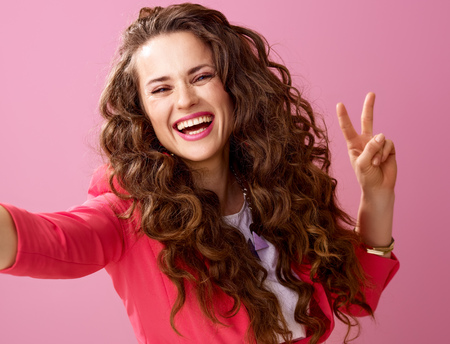 Pink Mood. happy young woman with long wavy brunette hair isolated on pink taking selfie and showing victory