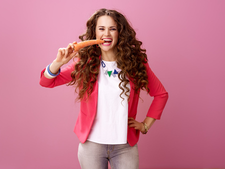 Pink Mood. smiling young woman with long wavy brunette hair isolated on pink eating carrot Banco de Imagens