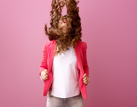 Pink Mood. smiling modern woman with long wavy brunette hair isolated on pink background shaking hair Stock Photo