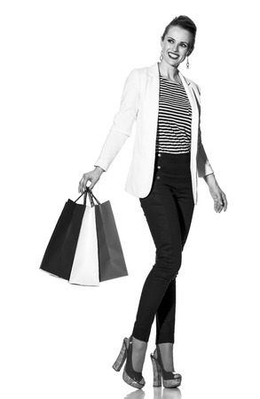 Luxury Shopping. The French way. Full length portrait of happy young woman in white jacket isolated on white with shopping bags painted in the color of the French flag looking at copy space Stock Photo