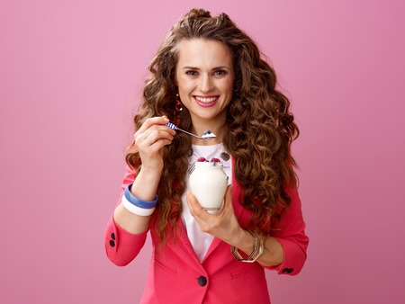 Pink Mood. Portrait of happy trendy woman with long wavy brunette hair isolated on pink background with farm organic yogurt