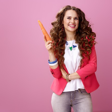 Pink Mood. smiling trendy woman with long wavy brunette hair on pink background with carrot got idea Banco de Imagens