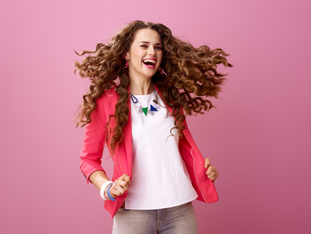 Pink Mood. smiling trendy woman with long wavy brunette hair isolated on pink shaking hair