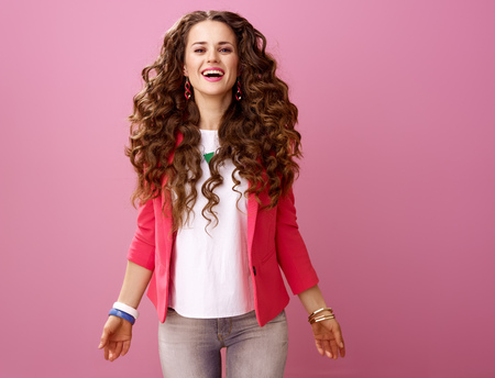 Pink Mood. Portrait of happy stylish woman with long wavy brunette hair isolated on pink background