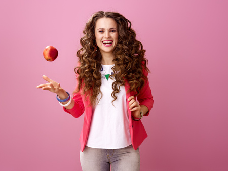 Pink Mood. smiling trendy woman with long wavy brunette hair on pink background throwing up an apple Фото со стока