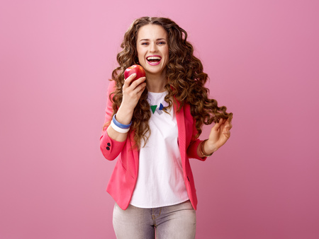 Pink Mood. happy stylish woman with long wavy brunette hair on pink background eating an apple Banco de Imagens