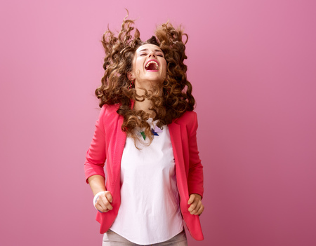 Pink Mood. smiling stylish woman with long wavy brunette hair isolated on pink shaking hair Stock Photo