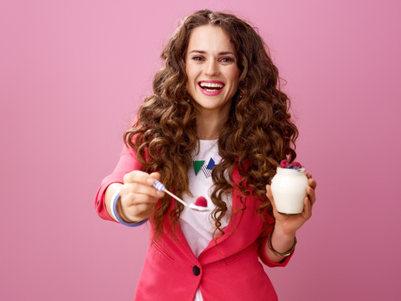 Pink Mood. happy young woman with long wavy brunette hair isolated on pink giving spoon with farm organic yogurt Фото со стока