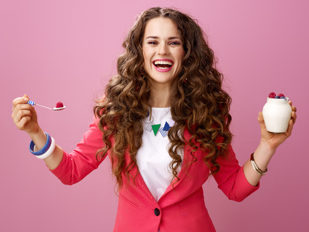 Pink Mood. smiling young woman with long wavy brunette hair isolated on pink with farm organic yogurt