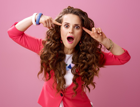 Pink Mood. Portrait of young crazy woman with long wavy brunette hair isolated on pink background Stock Photo