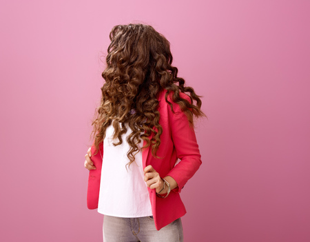 Pink Mood. Portrait of modern woman with long wavy brunette hair isolated on pink with the face covered by hair