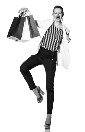 Luxury Shopping. The French way. Full length portrait of happy young fashion-monger in white jacket isolated on white showing shopping bags painted in the color of the French flag
