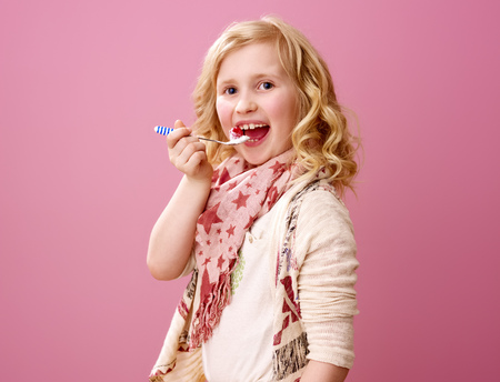 Pink mood. happy stylish child with wavy blonde hair isolated on pink eating farm organic yogurt