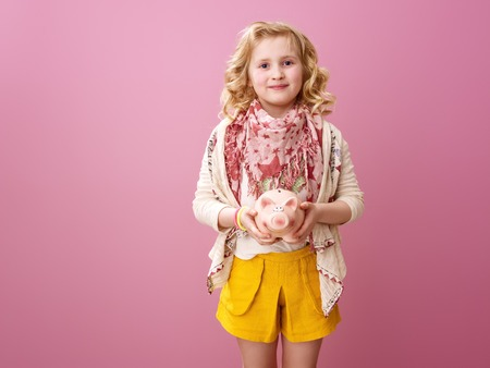 Pink mood. happy modern girl with wavy blonde hair on pink background with piggy bank