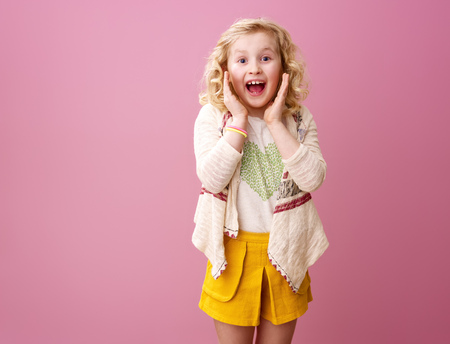 Pink mood. surprised modern girl with wavy blonde hair isolated on pink