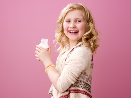 Pink mood. Portrait of smiling stylish child with wavy blonde hair on pink background with farm organic yogurt
