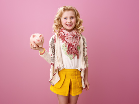 Pink mood. smiling modern child with wavy blonde hair isolated on pink holding piggy bank