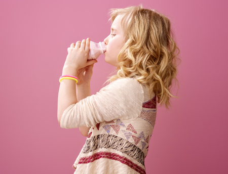 Pink mood. smiling modern girl with wavy blonde hair on pink background drinking farm organic yogurt