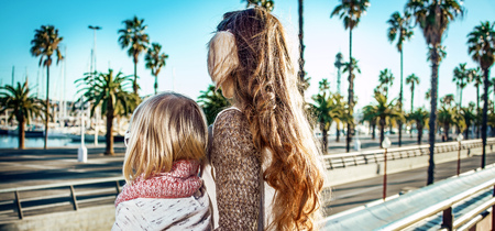 in Barcelona for a perfect winter. Seen from behind modern mother and daughter tourists in Barcelona, Spain