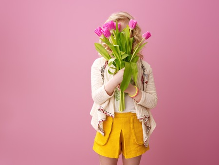Pink mood. modern girl with wavy blonde hair isolated on pink background hiding behind a bouquet of tulips