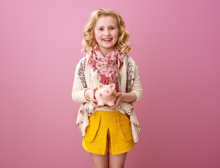 Pink mood. happy modern child with wavy blonde hair isolated on pink showing piggy bank