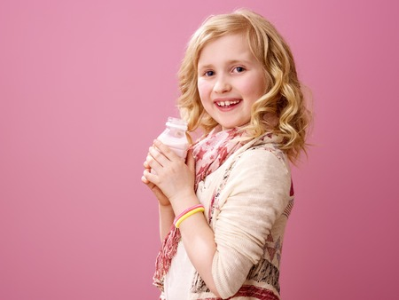 Pink mood. Portrait of smiling stylish girl with wavy blonde hair isolated on pink background with farm organic yogurt