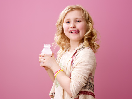 Pink mood. smiling stylish girl with wavy blonde hair isolated on pink background with delicious farm organic yogurt licking lips