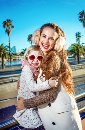 in Barcelona for a perfect winter. Portrait of happy young mother and child travellers in Barcelona, Spain embracing