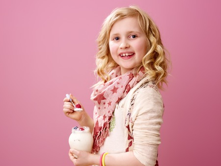 Pink mood. happy modern child with wavy blonde hair isolated on pink background eating farm organic yogurt