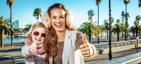 in Barcelona for a perfect winter. happy young mother and child tourists in Barcelona, Spain showing thumbs up Stock fotó