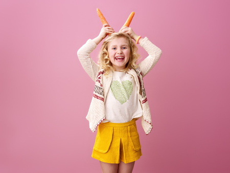Pink mood. happy stylish girl with wavy blonde hair on pink background making horns from carrots