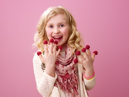 Pink mood. smiling stylish girl with wavy blonde hair on pink background eating raspberries on the fingers Stock Photo