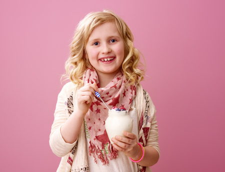 Pink mood. Portrait of smiling stylish child with wavy blonde hair isolated on pink background eating farm organic yogurt Фото со стока