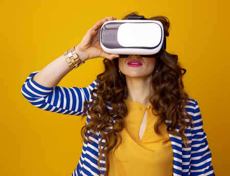 Portrait of trendy woman in striped jacket against yellow background in VR headset