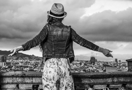 Perfect evening with stunning view. Seen from behind trendy woman in long dress and straw hat in the front of cityscape of Barcelona, Spain rejoicing