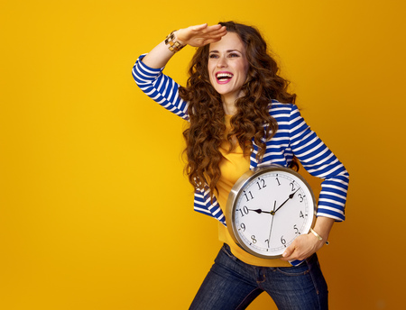 happy trendy woman with long wavy brunette hair on yellow background with clock looking at copy space
