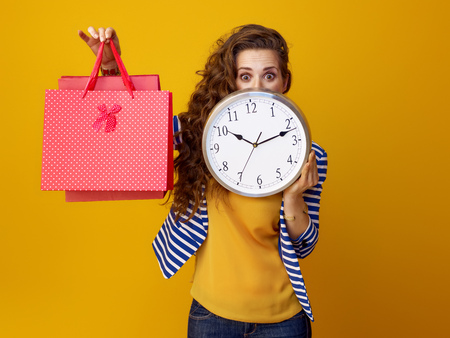 surprised trendy woman with long wavy brunette hair on yellow background hiding behind clock and showing shopping bags Stock Photo