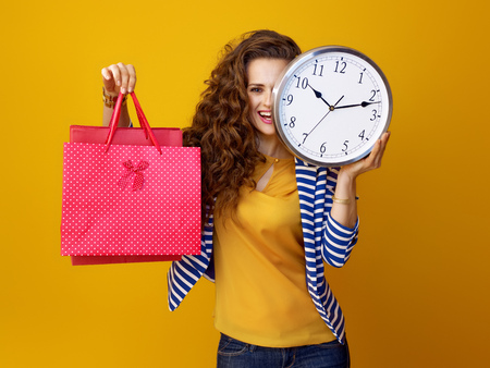 smiling young woman with long wavy brunette hair against yellow background with clock and shopping bags