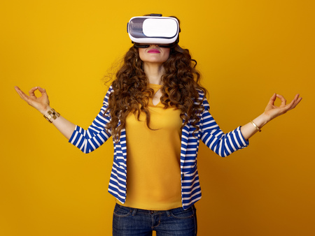 relaxed modern woman with long wavy brunette hair against yellow background in virtual reality headset Stok Fotoğraf - 97383825