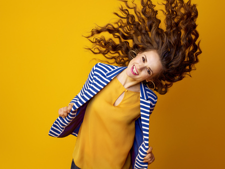 cheerful young woman in striped jacket on yellow background shaking hair