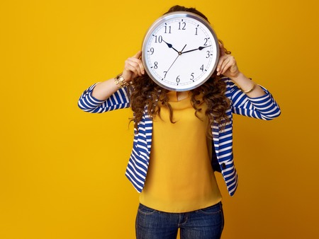 young woman in striped jacket isolated on yellow background holding clock in the front of face 版權商用圖片