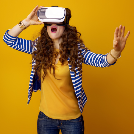 surprised modern woman with long wavy brunette hair against yellow background in virtual reality headset