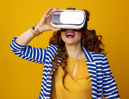 Portrait of happy modern woman with long wavy brunette hair isolated on yellow background in VR headset Stok Fotoğraf