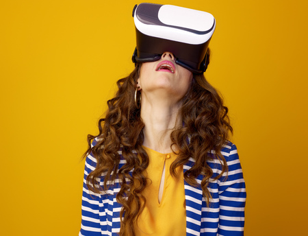 tired young woman with long wavy brunette hair isolated on yellow wearing virtual reality headset Stok Fotoğraf - 97384051