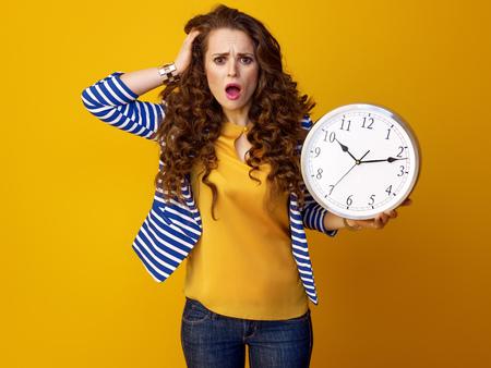 時計を示す黄色の背景に長い波状のブルネットの髪を持つ強調されたトレンディな女性 写真素材
