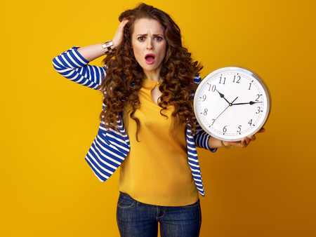 stressed trendy woman with long wavy brunette hair on yellow background showing clock Stok Fotoğraf